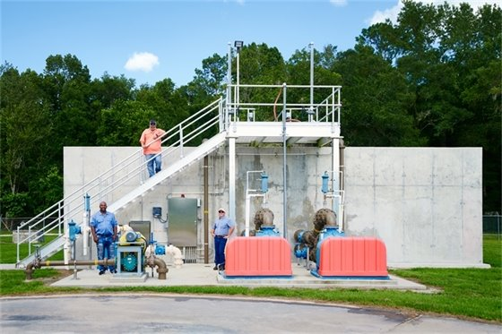 Wastewater treatment facility with workers standing by the tank