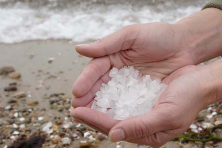 Cupped hands holding salt crystals by the sea