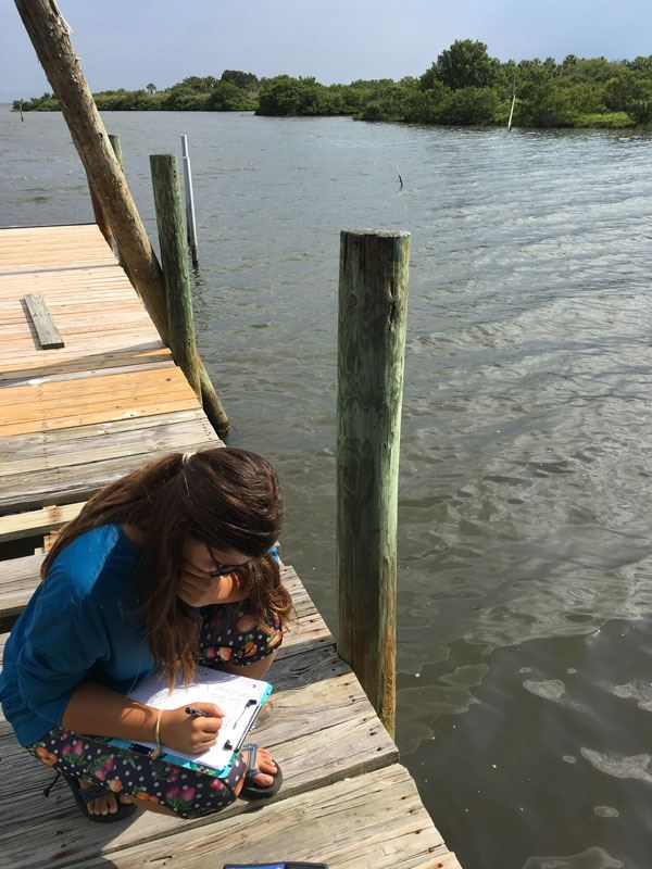 Juliana Navarro on a dock collecting data on mangroves