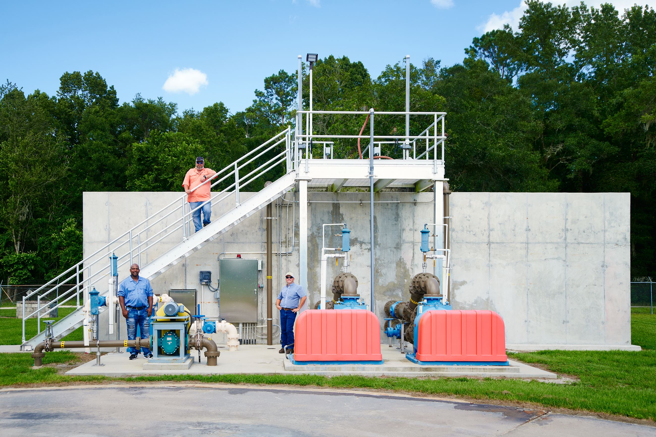 Wastewater treatment plant with staff standing along it.