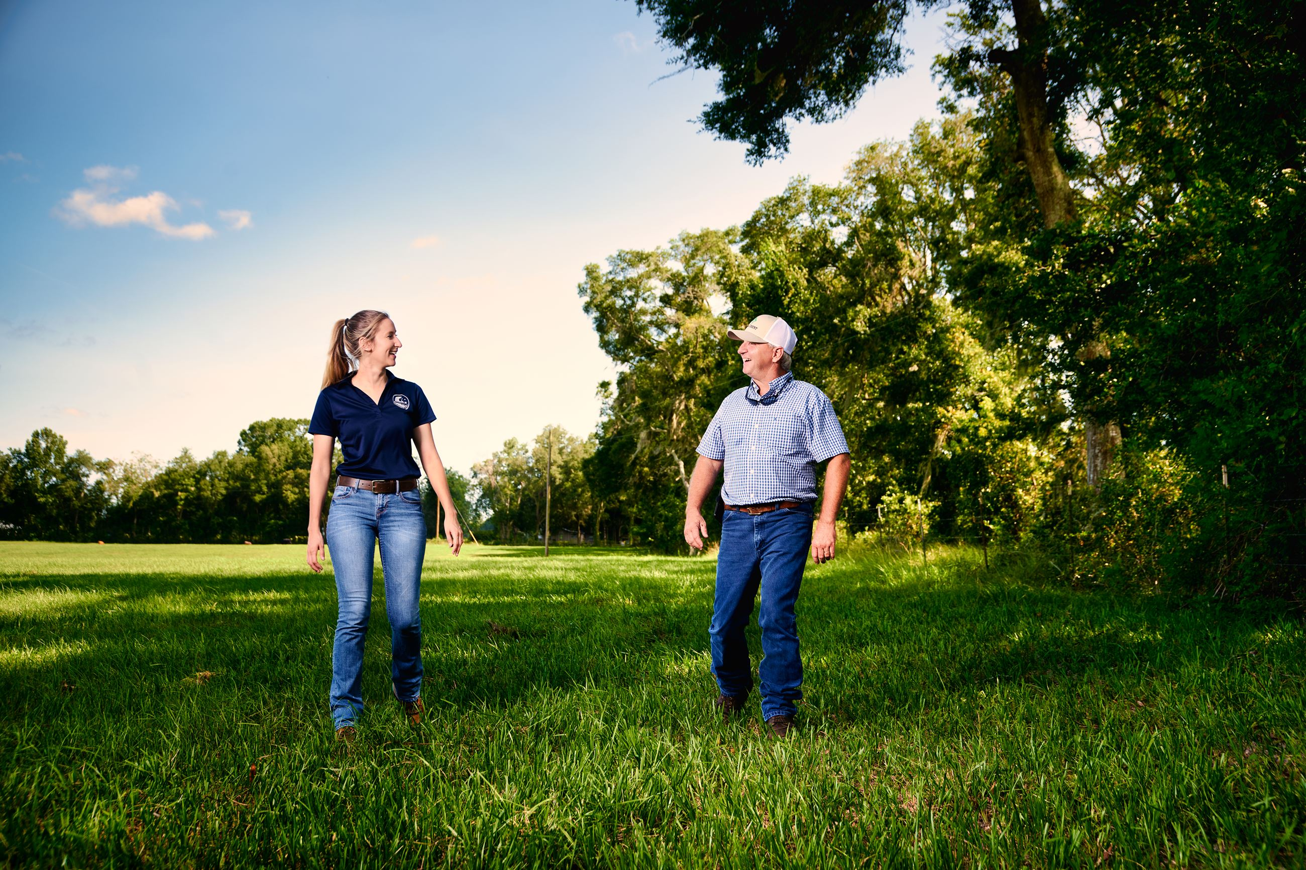 Two people walking in a pasture lined with trees.